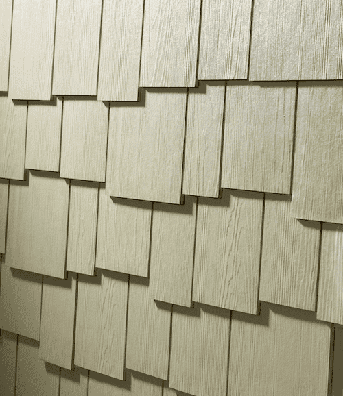 Close-up of staggered shingle siding in an off-white color with a cedar finish.