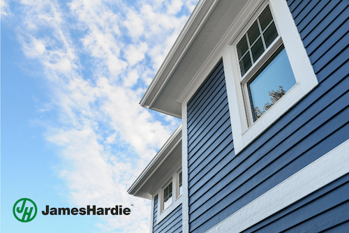 A house with blue lap siding and white trim angled upwards with a blue sky in the background. A James Hardie logo is in the bottom left corner of the image.
