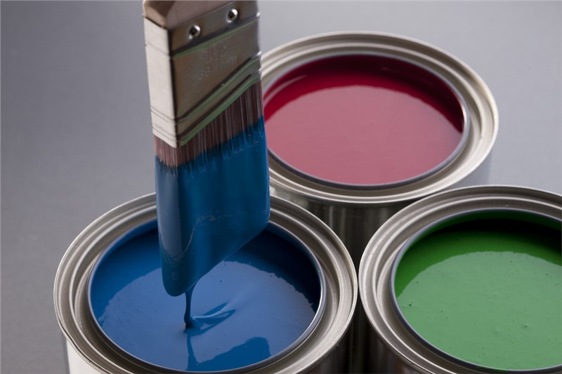 A studio image with three silver paint cans filled with blue, red, and green paint with a paint brush coming out of the blue can coated in paint.
