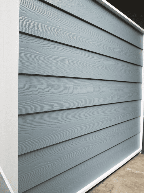 A show wall of traditional horizontal lap siding with a cedar finish. It is a baby blue color.
