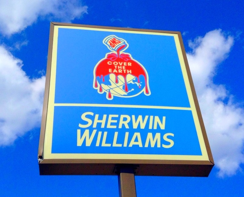 """A Sherwin-Williams store sign against a blue sky with clouds. The sign is bright blue with red detailing. A can of paint is pouring over an earth graphic with the words """"Cover the earth."""""""