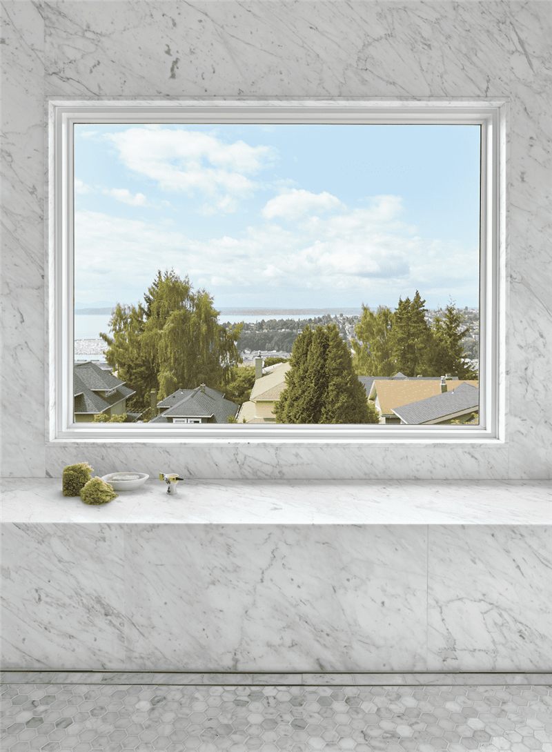 An image of a window in a gray slate room with a blue sky and green trees out the window.