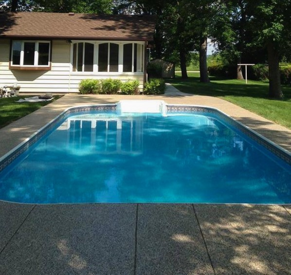 A backyard with a rectangular swimming pool with concrete surrounding. There is a house in the background with green grass and tall trees.