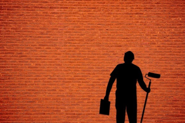 An orange brick wall with the shadow of a man standing with a paint can in his left hand and holding a long, rolling paint brush in his right hand.