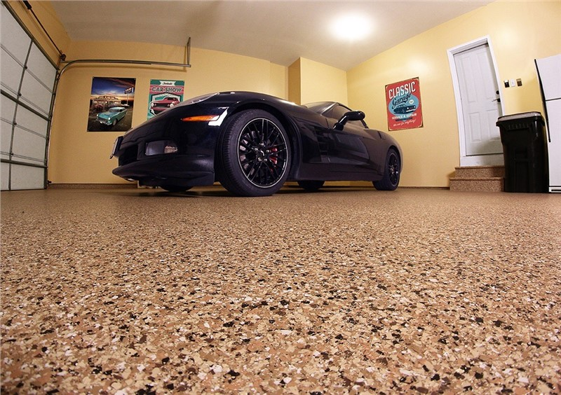 A black sports car in a garage with a floor that looks like brown granite with lots of flecks.