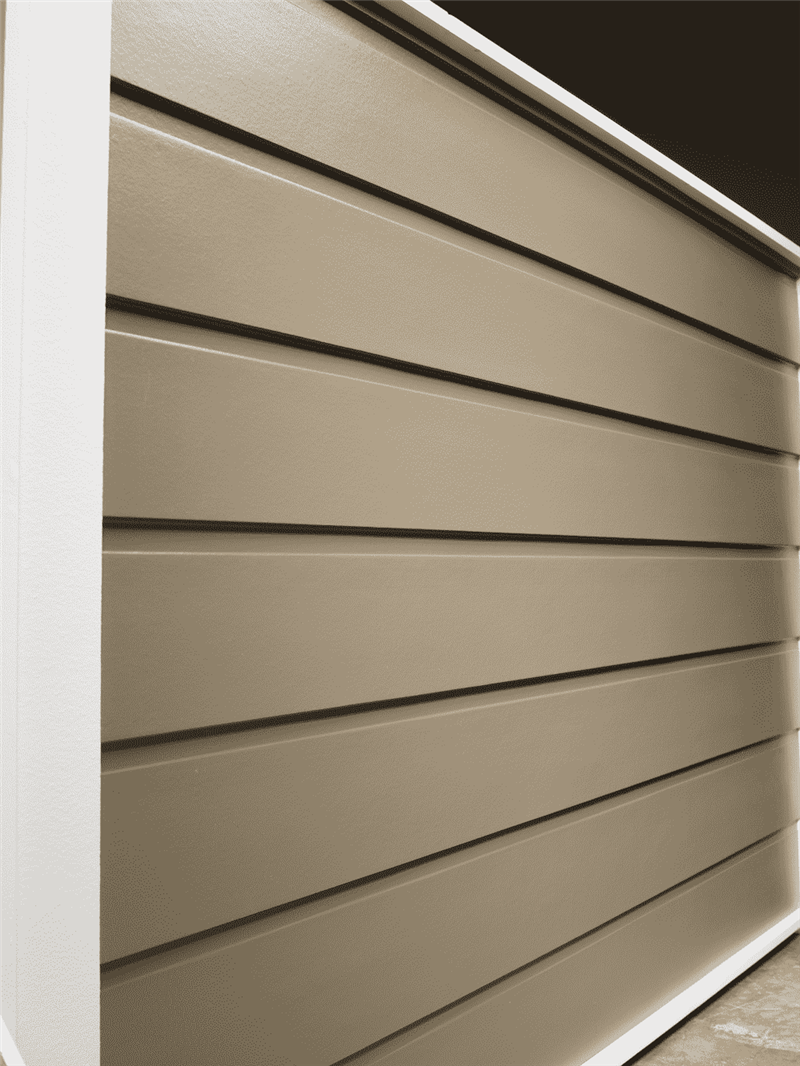A wall of dutch smooth horizontal siding in a dark beige color.