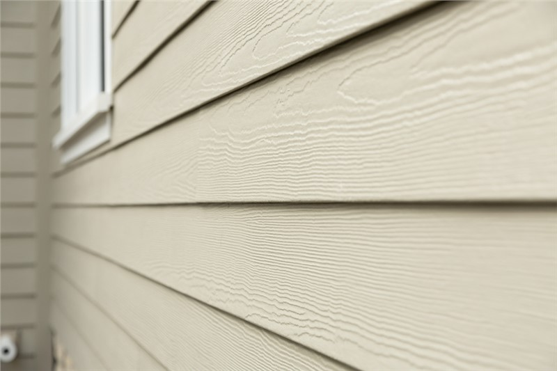 A close shot of the side of a home at an angle. The horizontal lap siding is a beige color with a cedar finish.