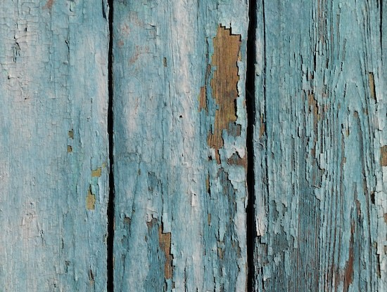 A close up of a vertical wood exterior with turquoise colored paint that is chipping to expose the wood.