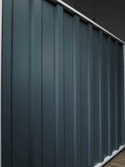Vertical board and batten siding in a smooth finish in navy color.