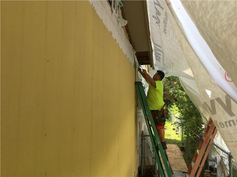A man in a bright yellow shirt standing on a ladder against a yellow wall with a tarp draping over both of them while the siding is being replaced.