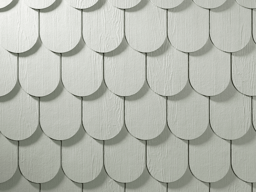 Close-up of scalloped shingle siding in white with a cedar finish.